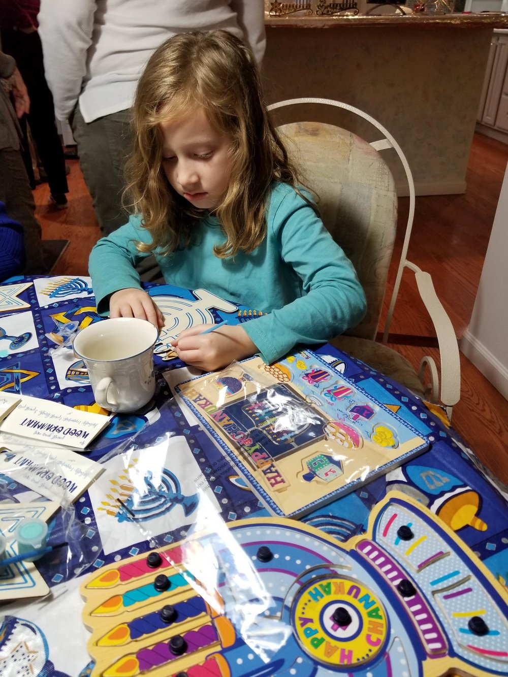 Sophia Finkel decorates a Hanukah menorah.jpg
