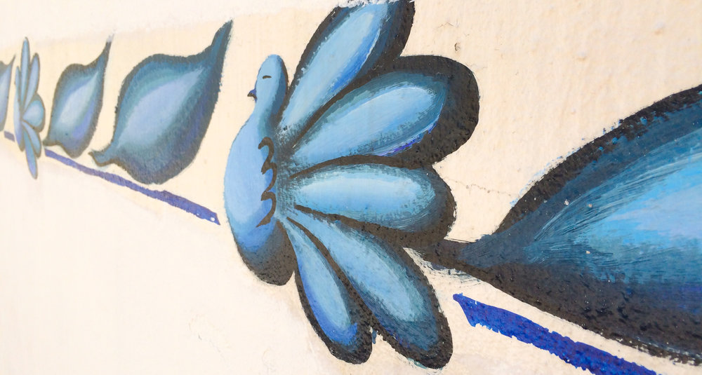 There are surprising pops of color, largely various shades of blue,scattered throughout the island of Crete. A blue door. A blue scattering of flowers painted on a boat. A string of blue birds that lured us inside a local artist's studio.