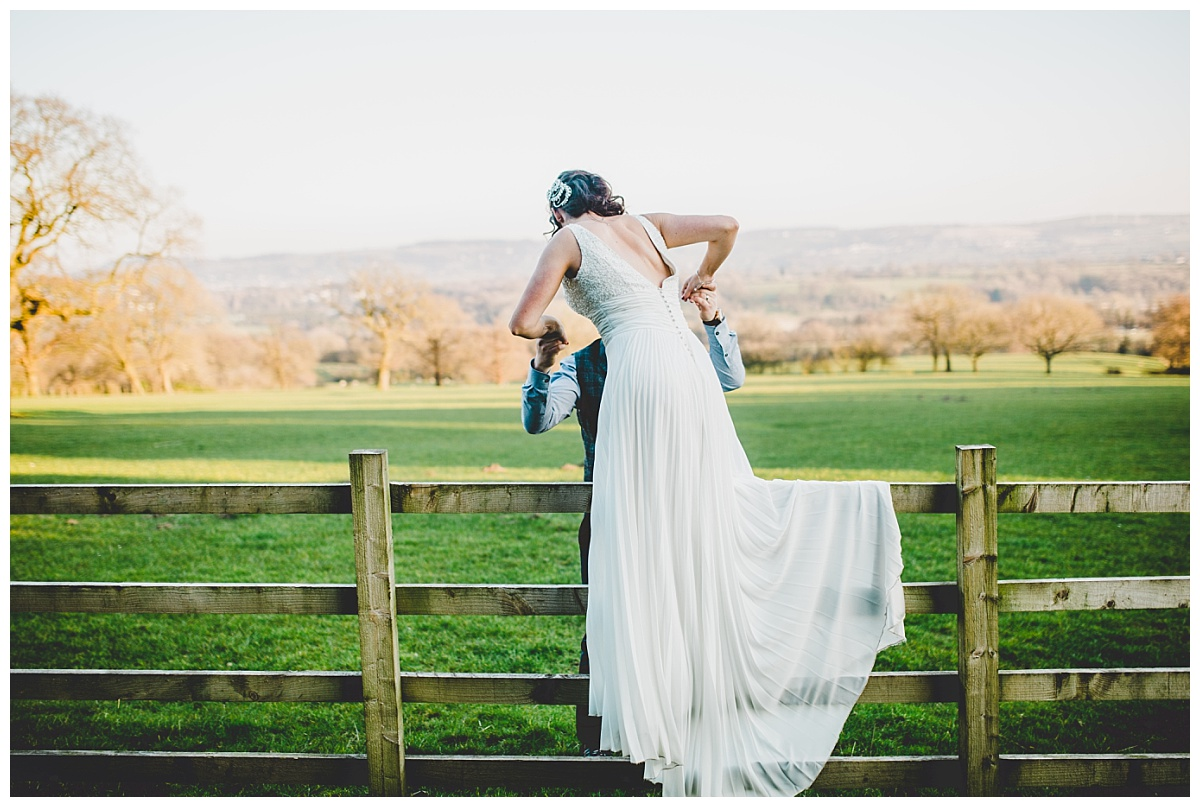 climbing over a fence at Shireburn Arms wedding in Lancashire