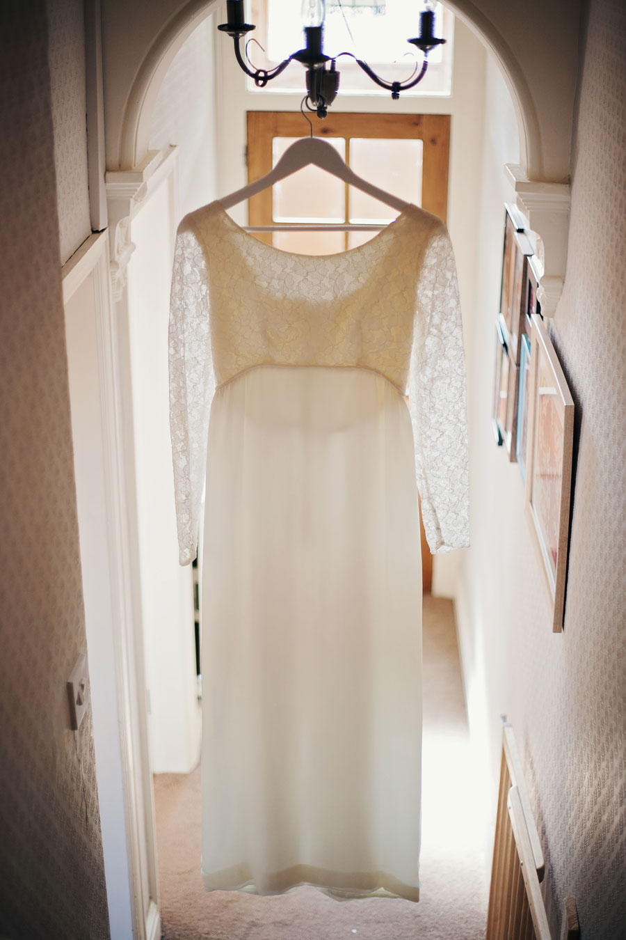 bride's dress hanging in hallway - vintage wedding photography in lancashire
