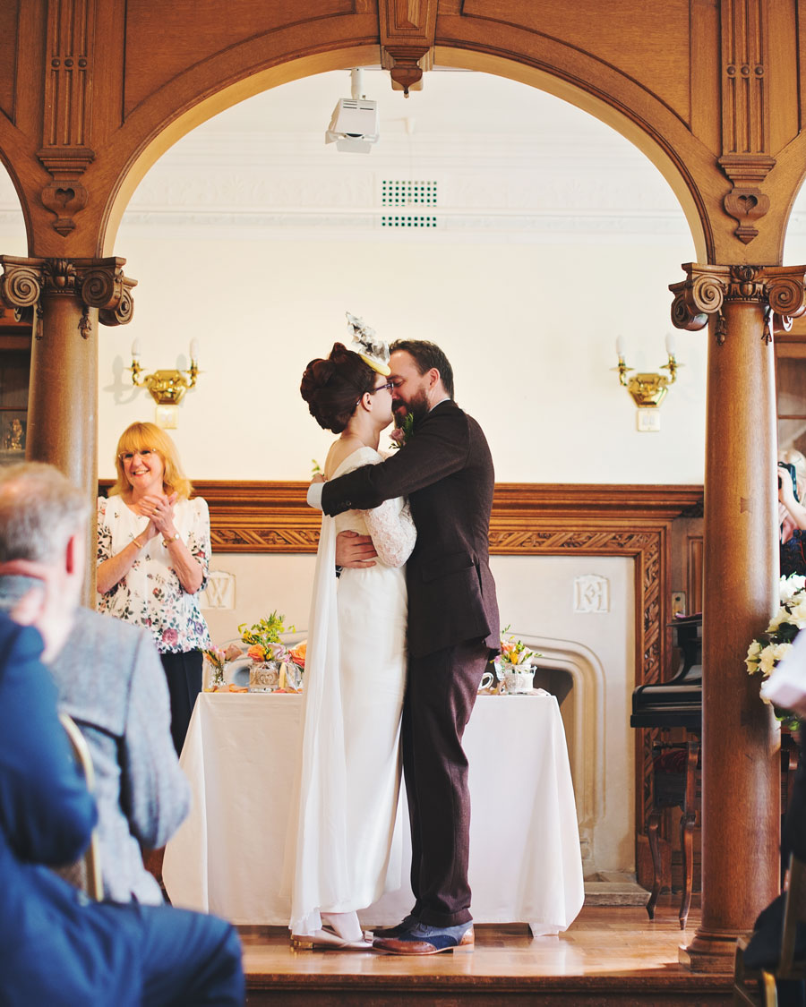 bride and groom first kiss during Haworth Art Gallery wedding ceremony