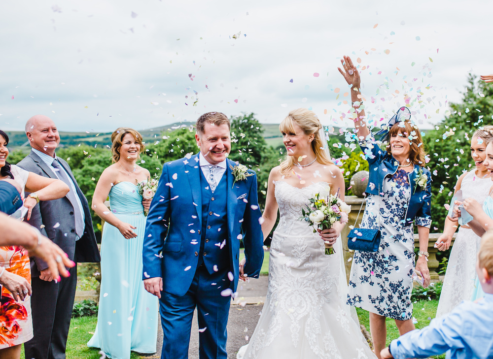 bride and groom walk through the confetti outside the haworth art gallery