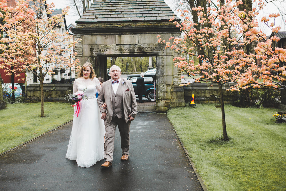 Bride and father walking into church - wedding photographer in cheshire