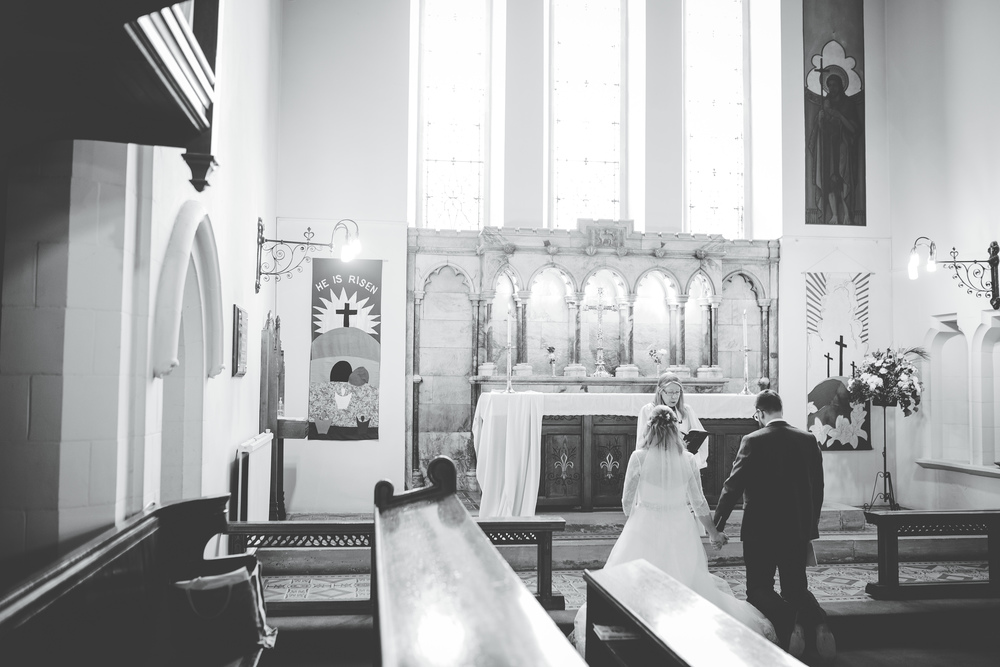 Artistic wedding photography in cheshire - bride and groom at the front of church