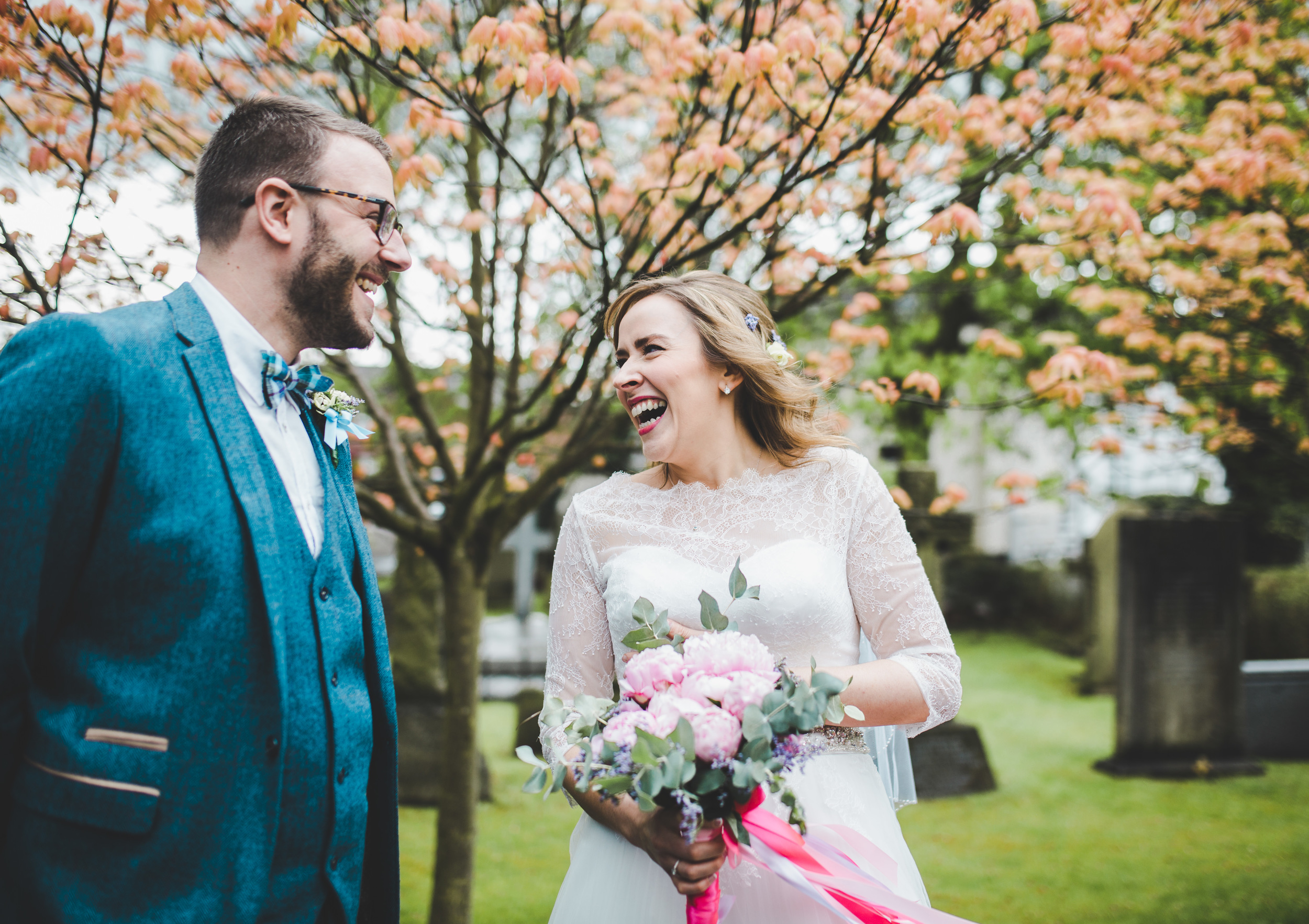 documentary wedding photography - bride and groom laugh outside church