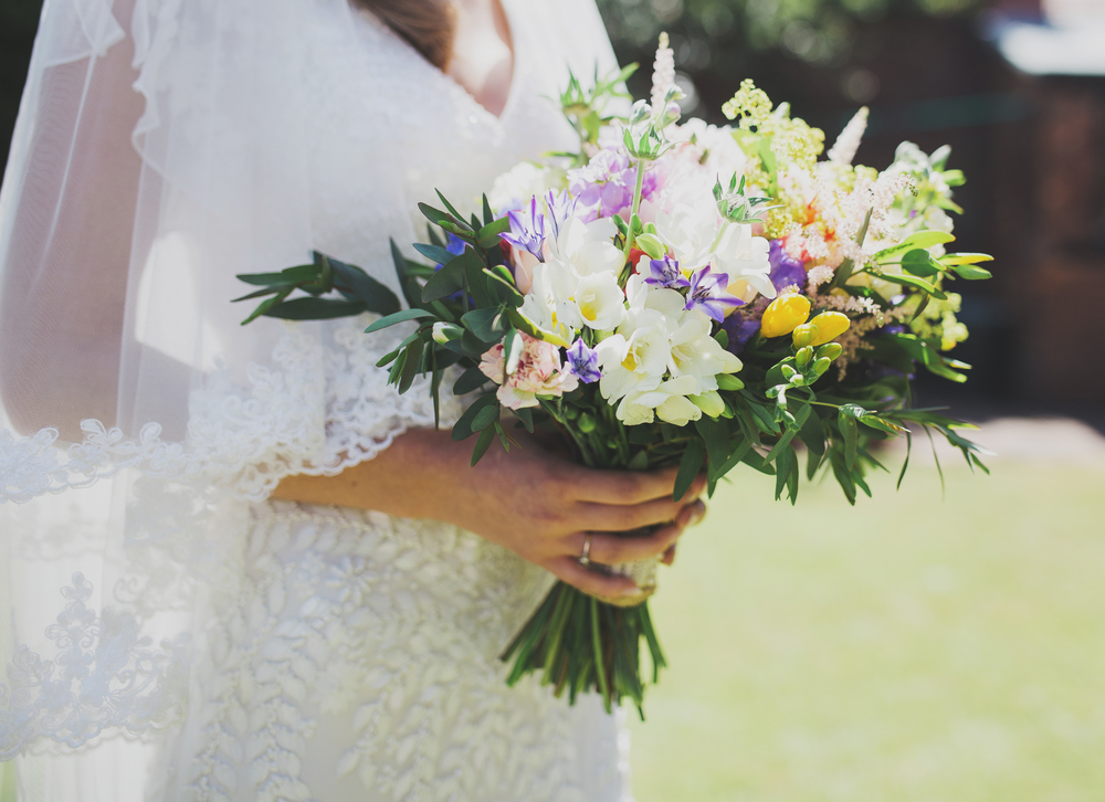 The bouquet  of flowers in the hand of the bride.