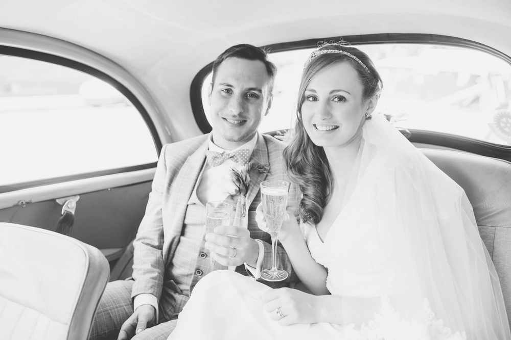 Black and white photograph of the bride and groom in the wedding car.