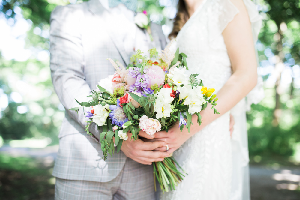 Documentary images of the Bride and groom holding the bouquet of flowers.