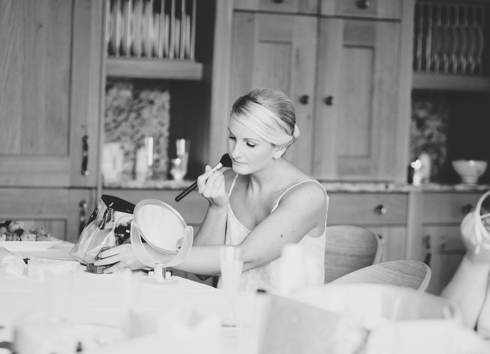 The bridemaid putting her makeup on at preston wedding
