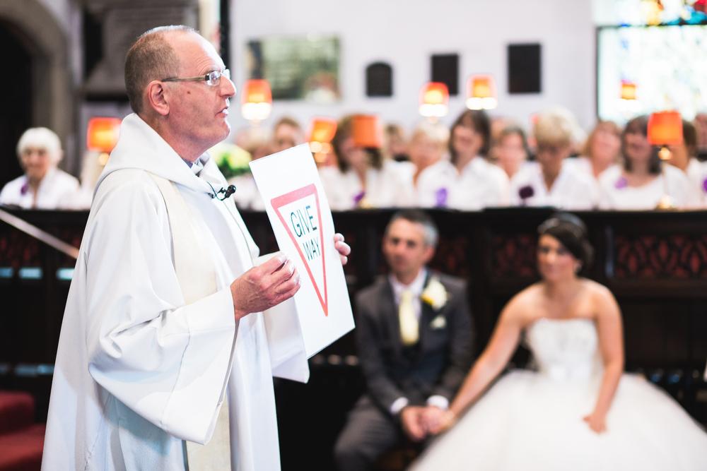 The vicar in church at preston wedding.
