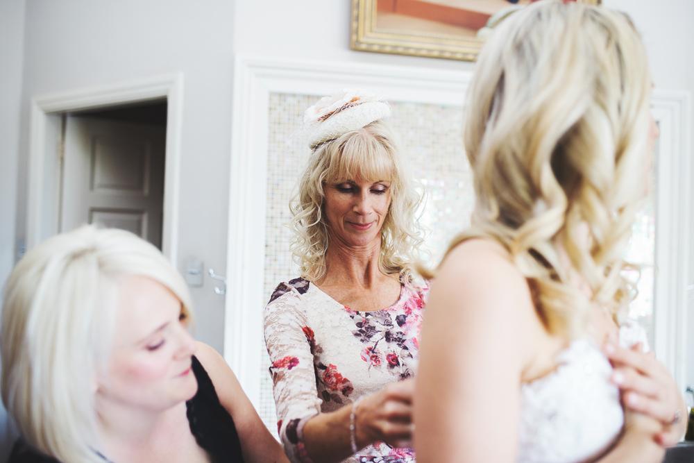 bride's mum getting her dressed - york wedding photogaphy