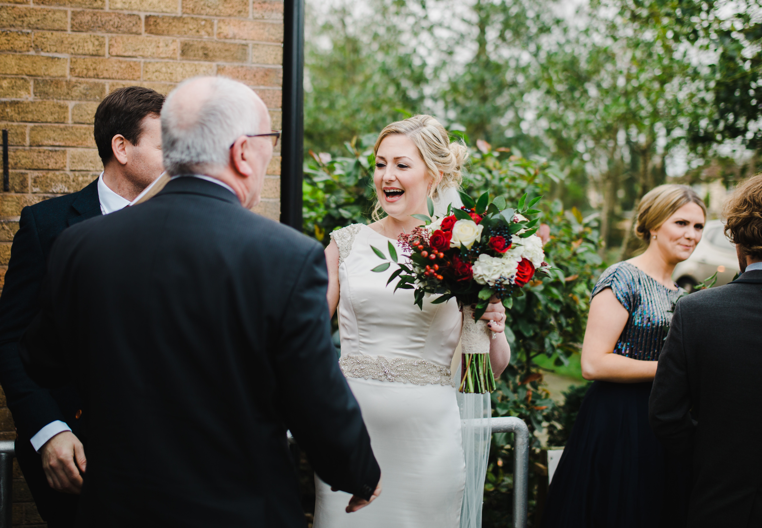 bride greets guests outside church