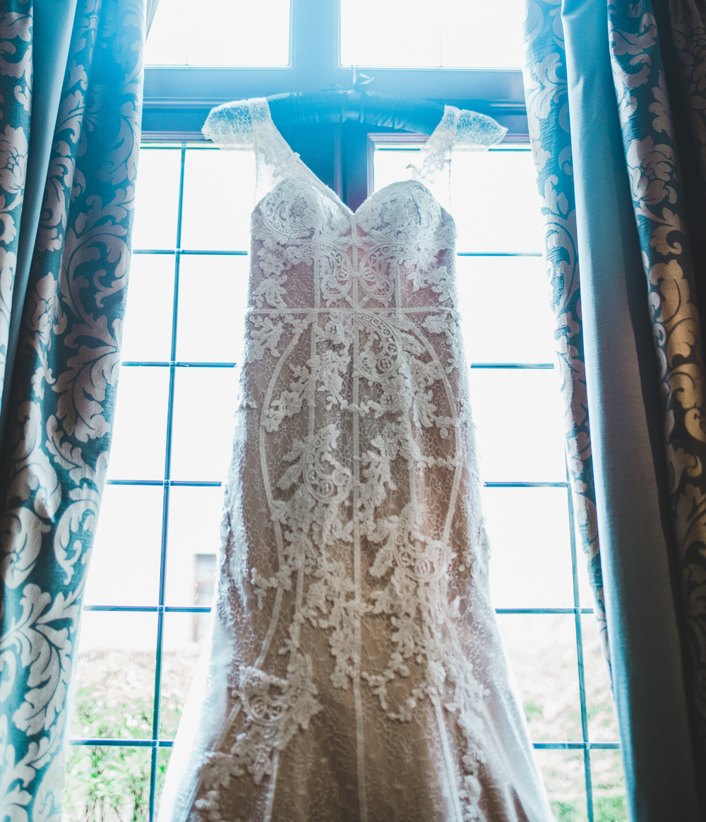 The wedding dress hung in the window before the big moment. -Cheshire wedding photography