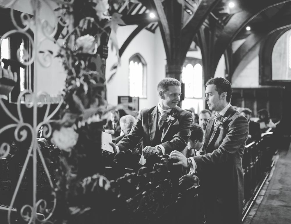Black and white documentary image of the groom waiting for his bride. Cheshire wedding photographer.