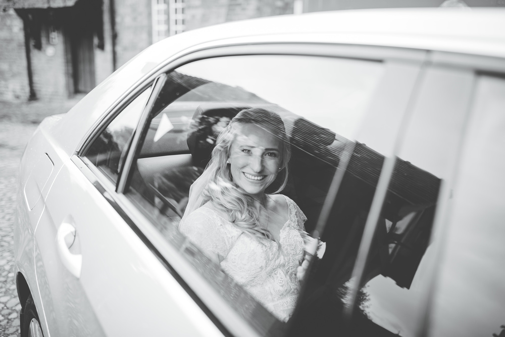 Black and white photo of the bride in the car. -Documentary wedding photography