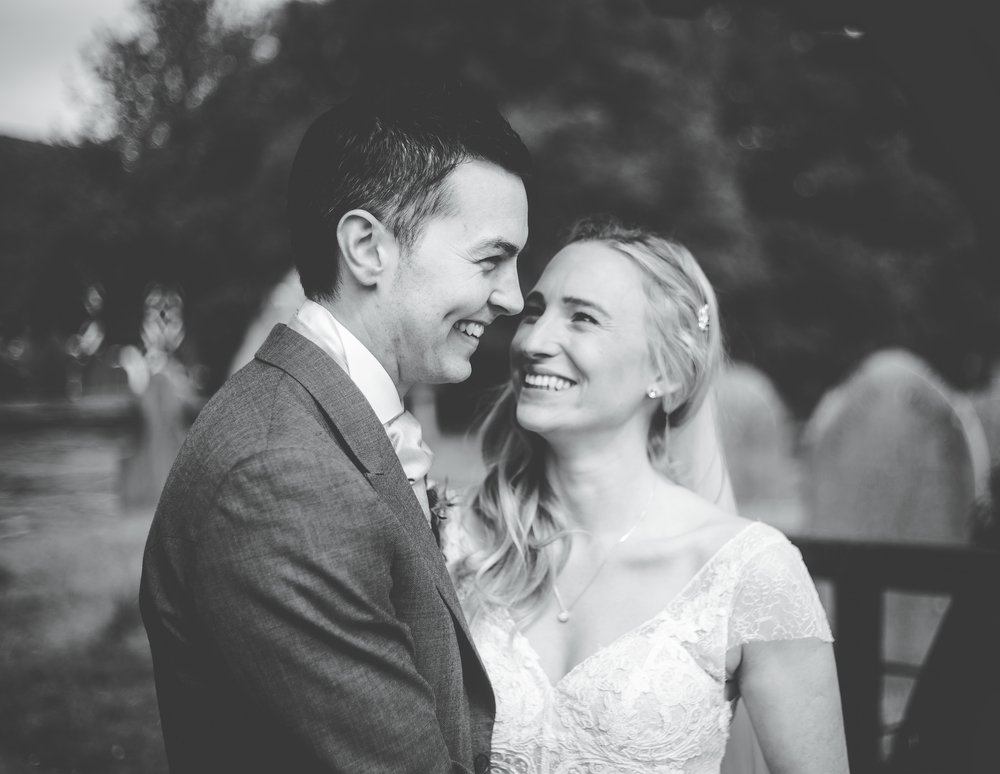Black and white photograph of the bride and groom smiling.