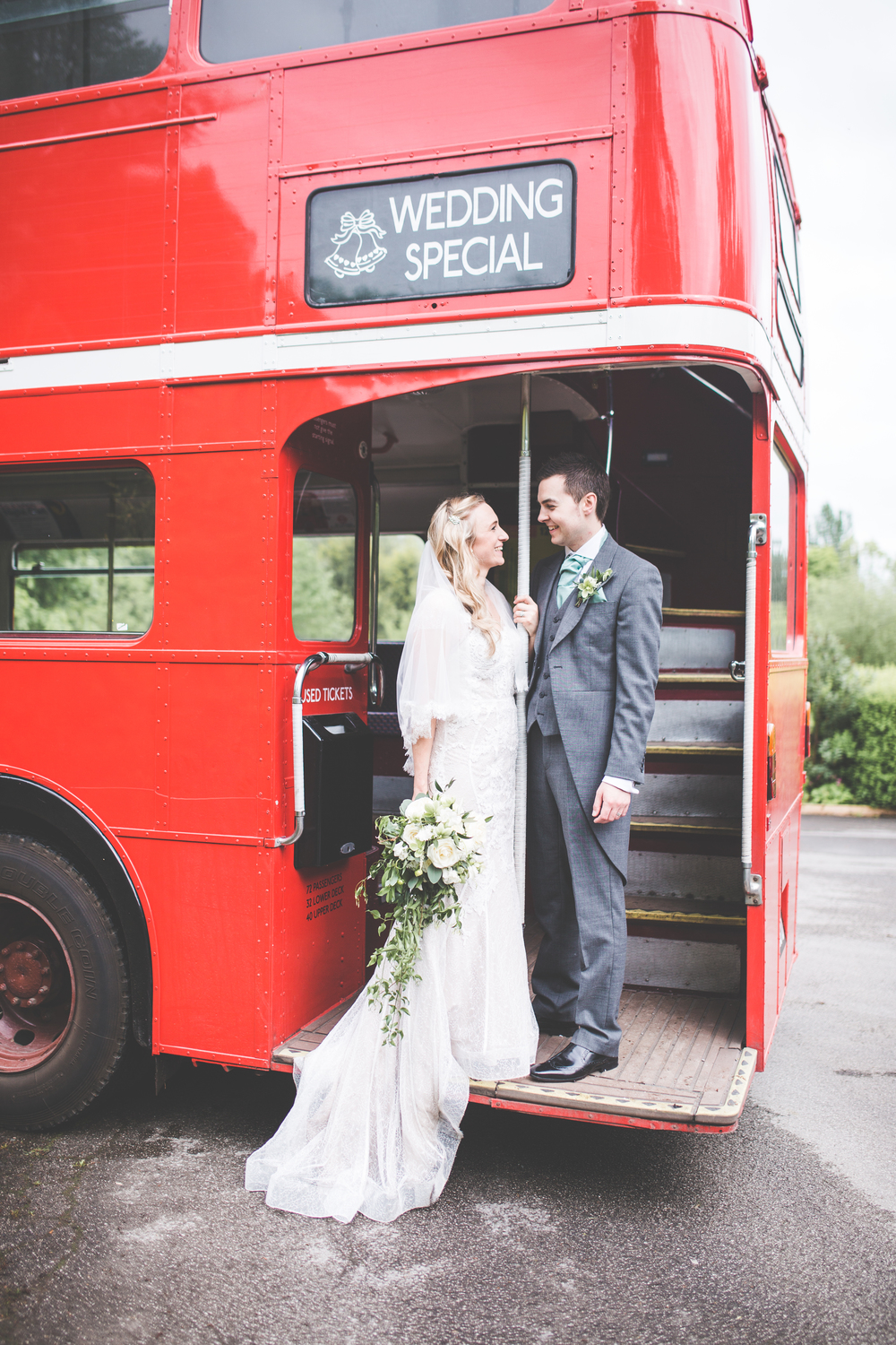 The bride and groom stood on the red double decker bus. -Wedding photography