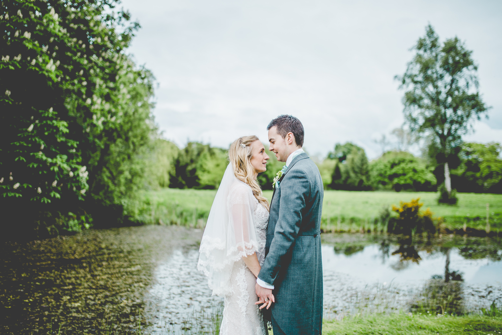 Bride and groom by the pond at The Oak Tree of Peover.