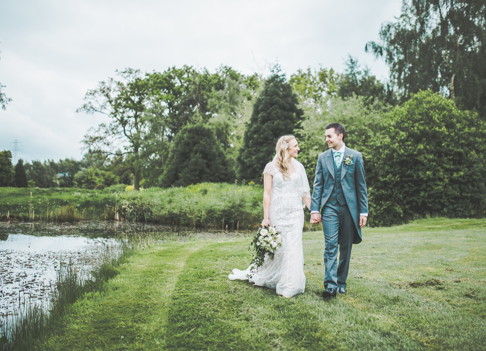 The bride and groom walking through the grass at The Oak Tree of Peover.