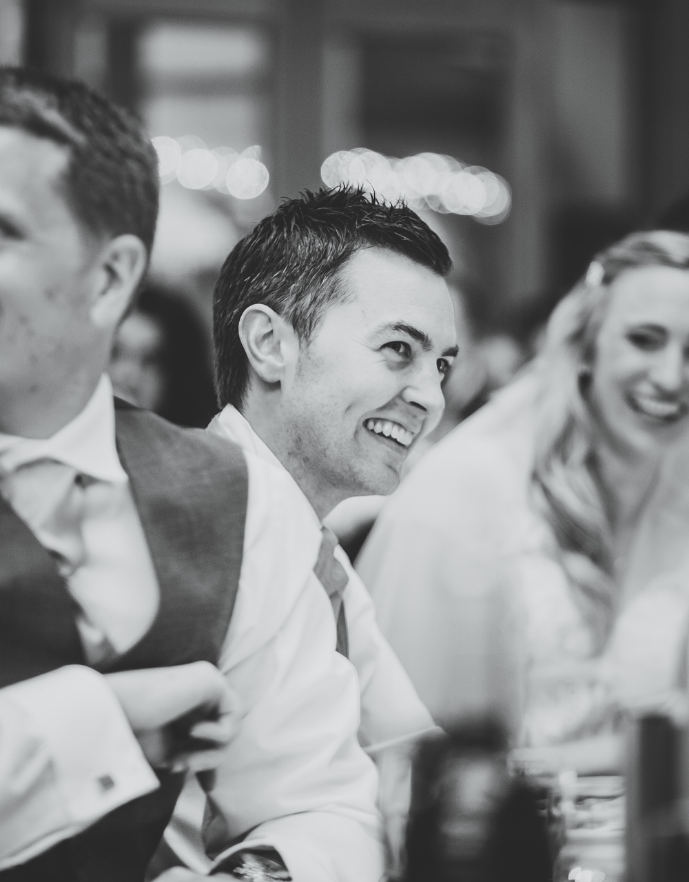 Black and white photo of a laughing guest. Cheshire wedding.