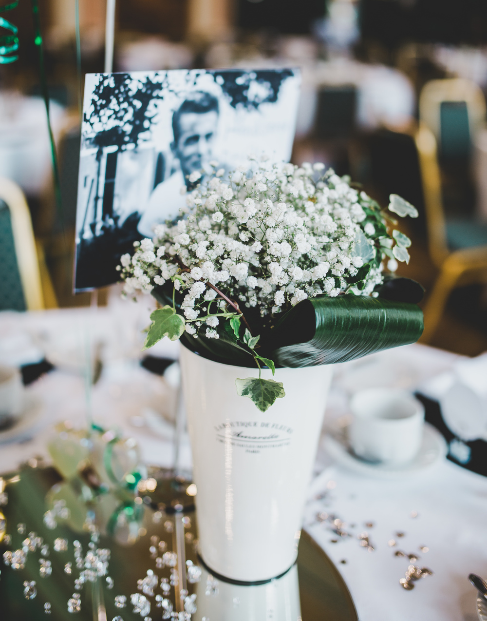 Beautiful table flowers surrounding an old photograph of the groom.