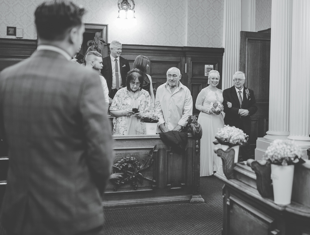 Black and white photograph of the bride walking to her groom with her father