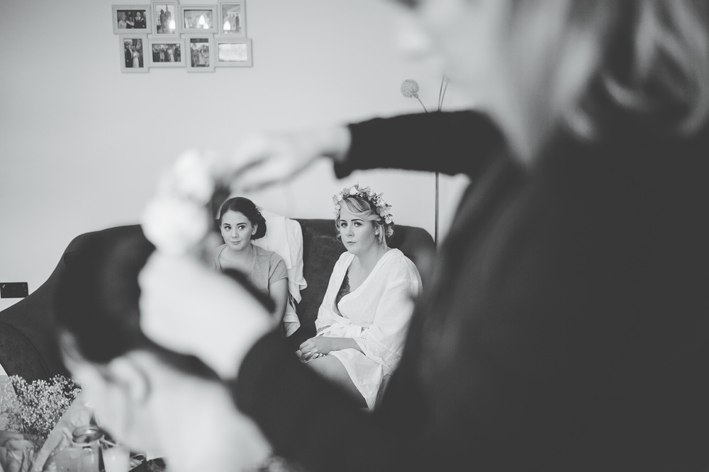 Black and white photograph of the bridesmaid getting her hair done.- Documentary photographer, Lancashire