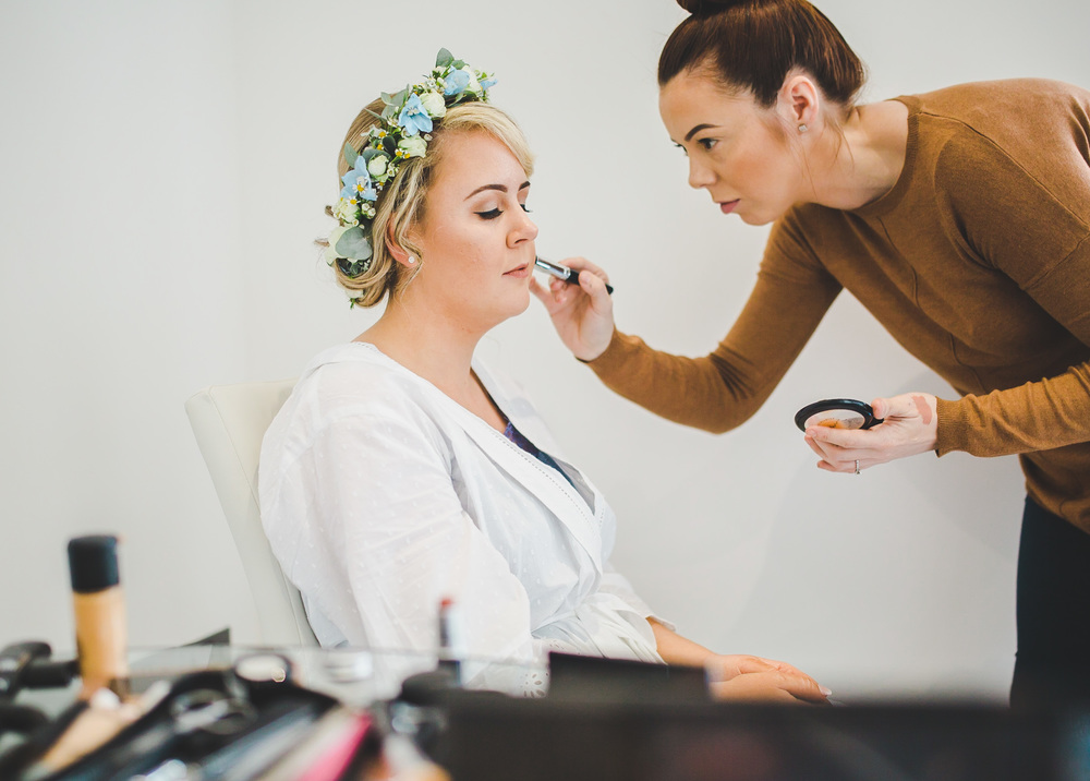 Documentary image of bride getting her makeup on.