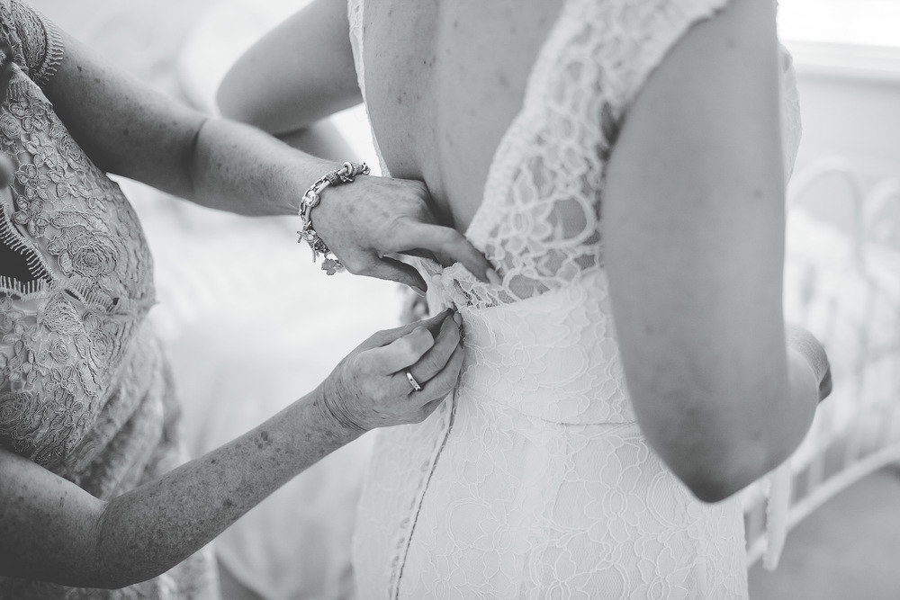 Black and white photograph of the bride getting her buttons done on her gown.-Vintage themed wedding