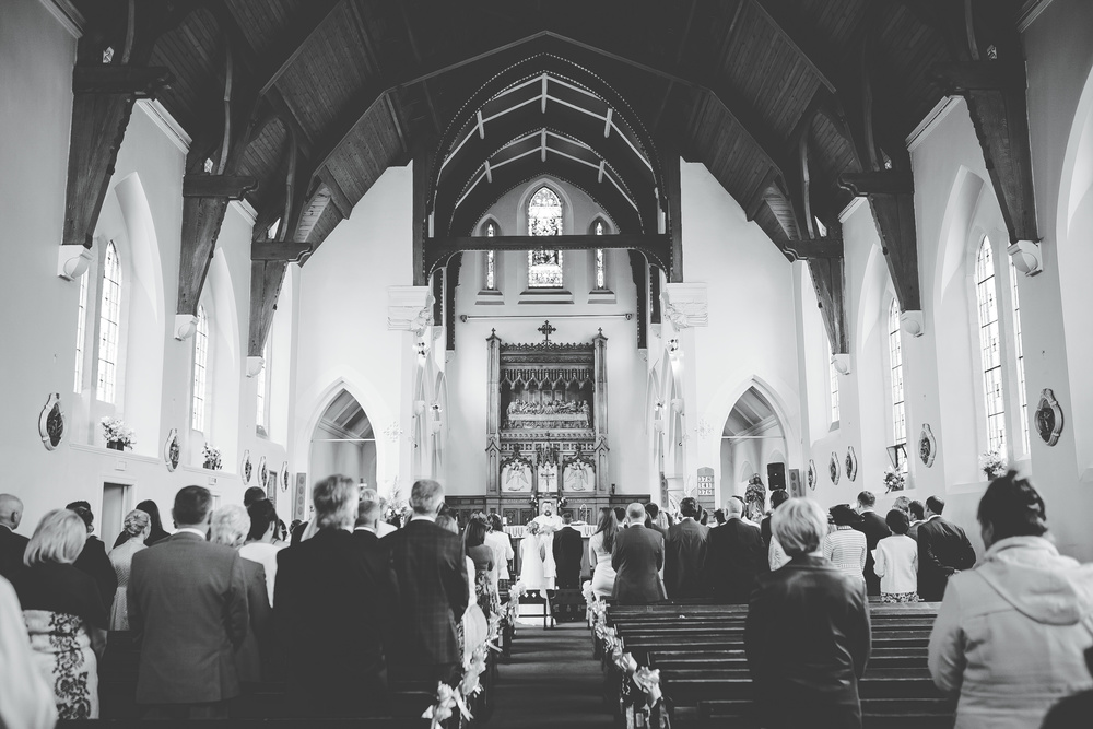Bride and groom walking down the aisle -Black and white photo of The Gorton Monastery wedding.