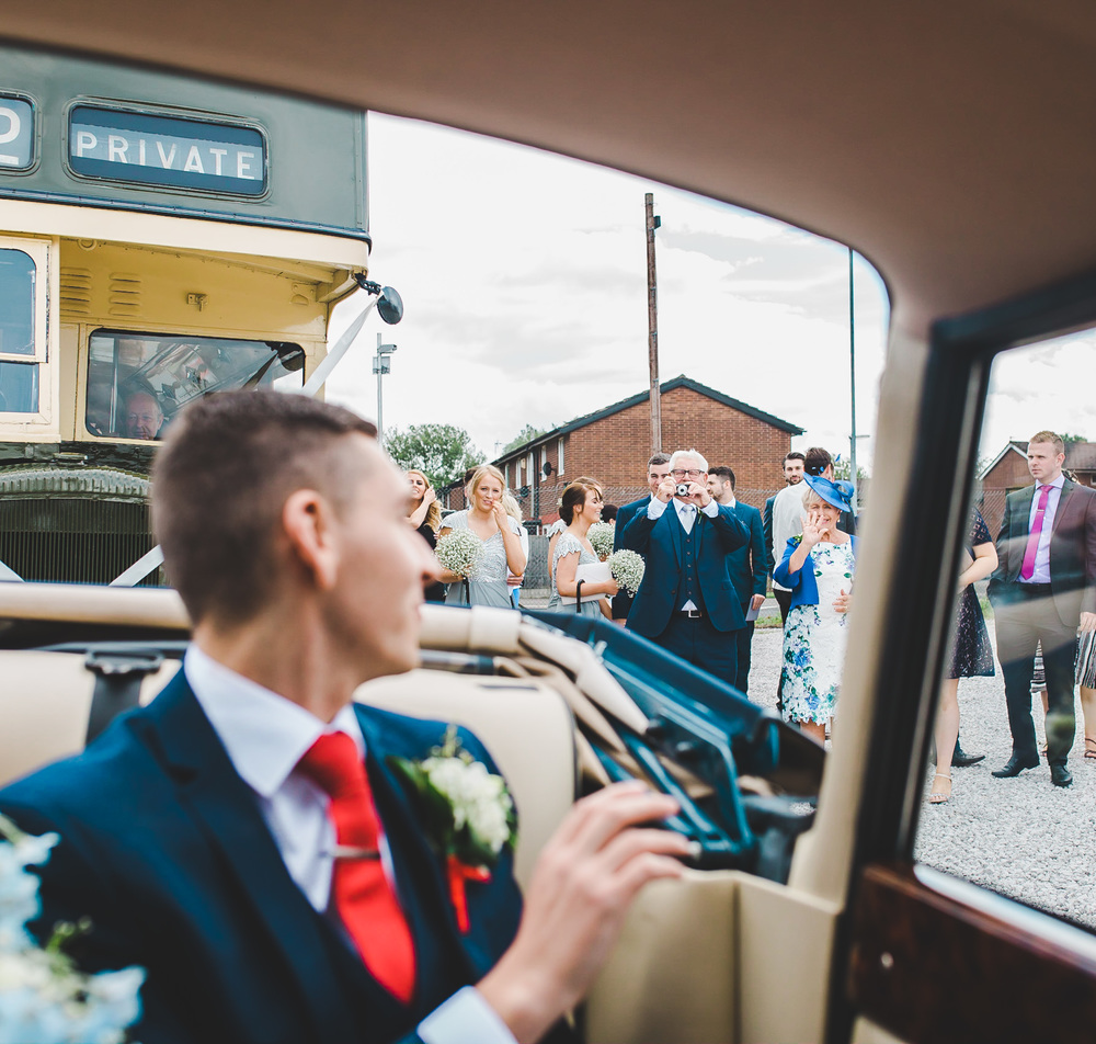 The groom in the back of his wedding car.- Lancashire photographer