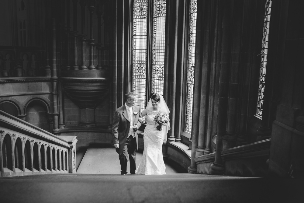 Father of the bride and bride walking up the stairs in the Manchester Town Hall.