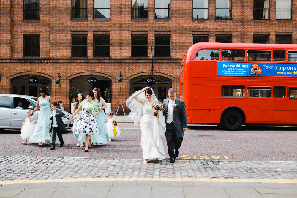 The bride, bridesmaid and her father crossing the road to Manchester Town Hall.
