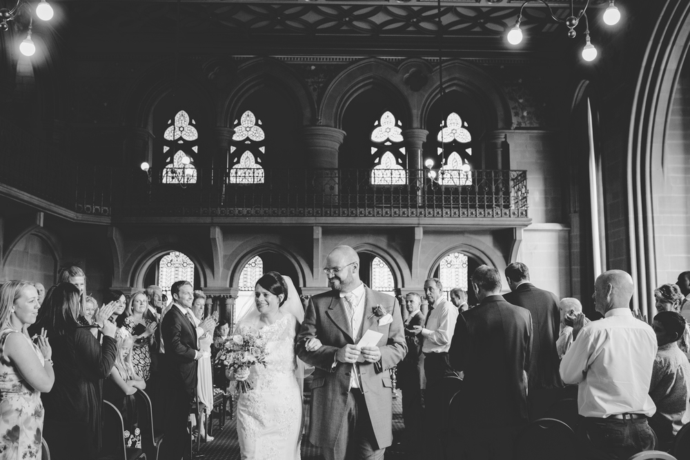 Black and white photograph of the bride and groom walking back down the aisle.