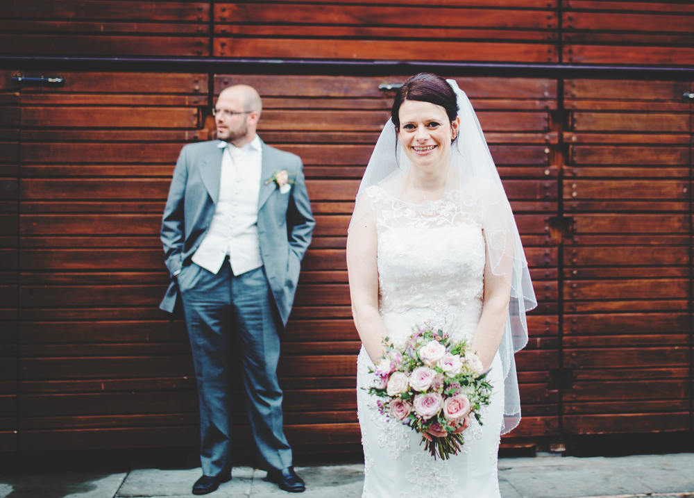 The groom and bride infant of a red wall. Manchester wedding photographer.