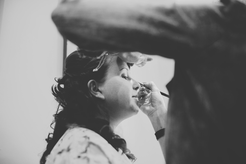 Black and white photograph of the bride getting her makeup done for the vintage wedding.- Documentary photographer
