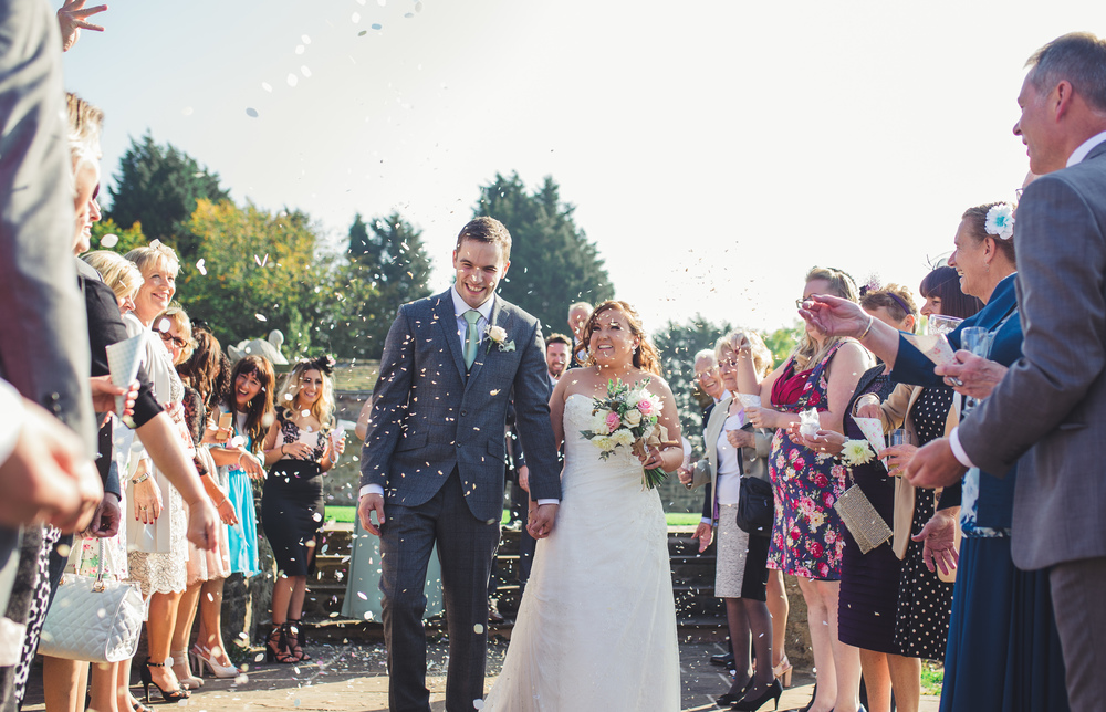 The bride and groom walking through confetti at the Lancashire wedding.
