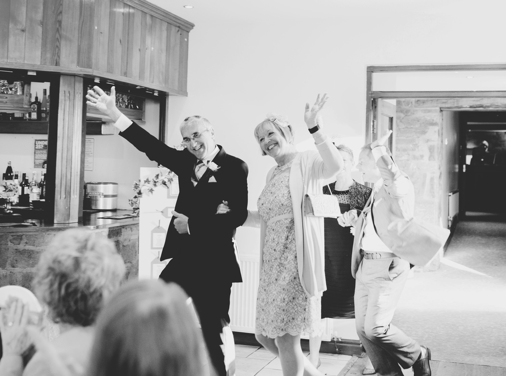 Black and white photo of waving wedding guests.- Lancashire wedding photographer.