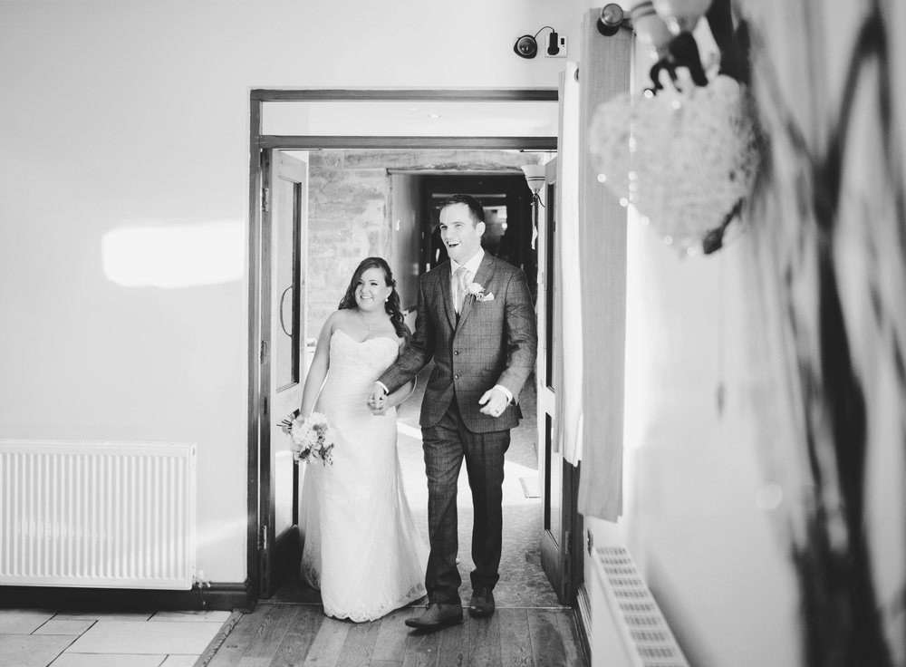 The bride and groom entering the reception room at Beeston Manor.