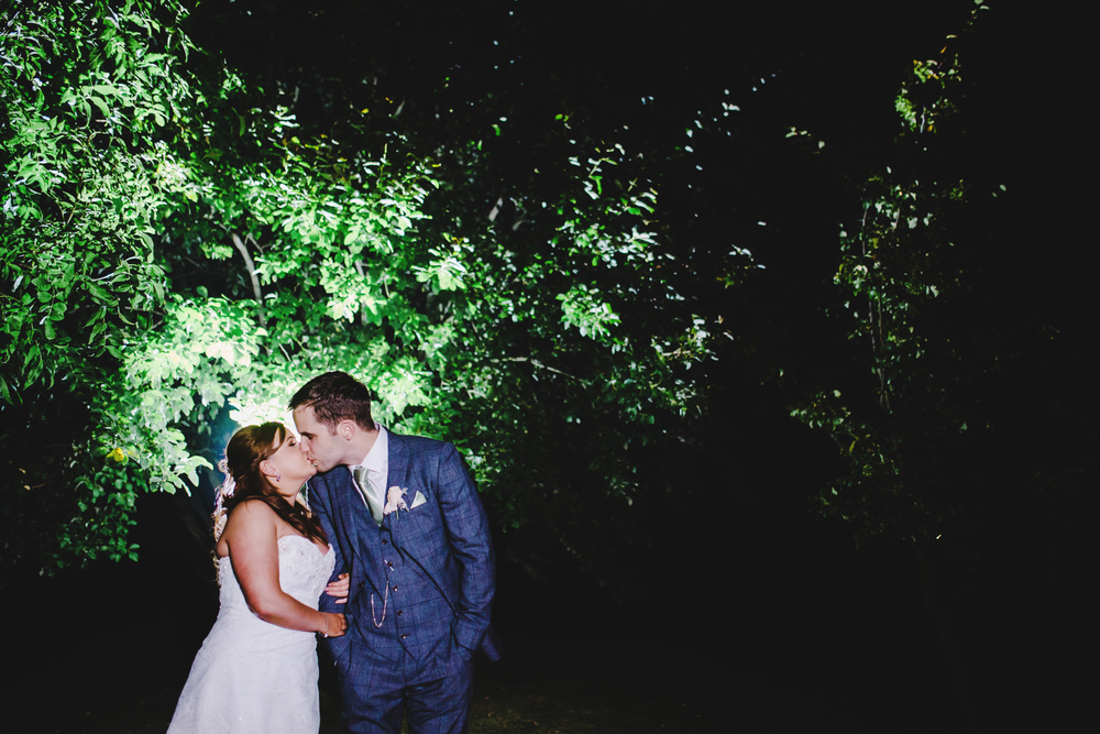 The bride and groom sharing a kiss surrounded by trees.- Lancashire wedding photography.