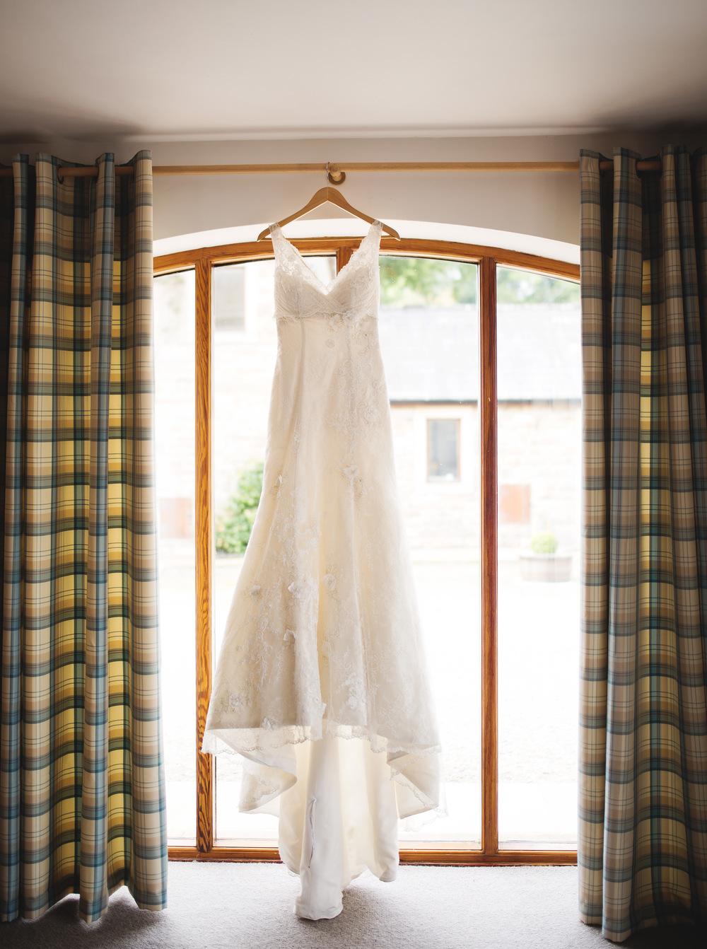 Bridal dress handing in the window- Lancashire wedding photogrpher.