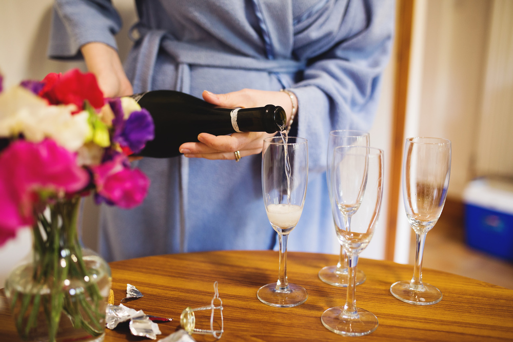 Pouring of the champagne at bridal prep. -Rustic theme wedding.