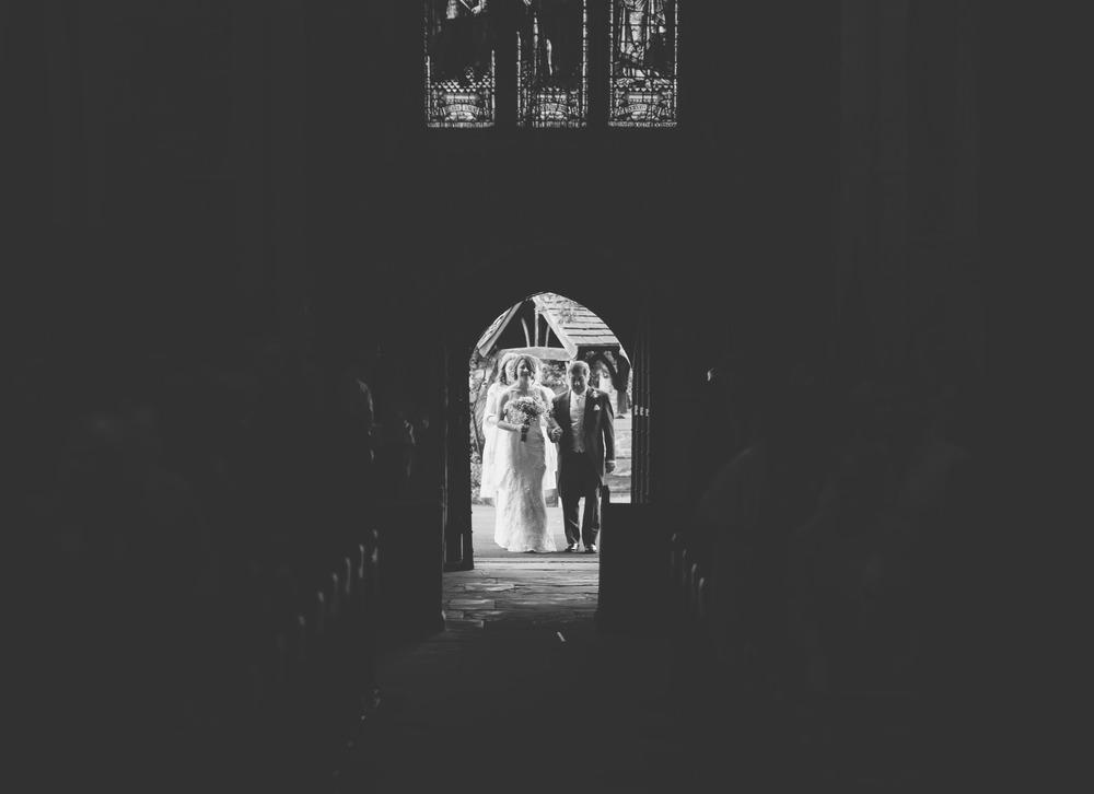 Creative wedding photographer photographs the bride walking into the weddin venue.