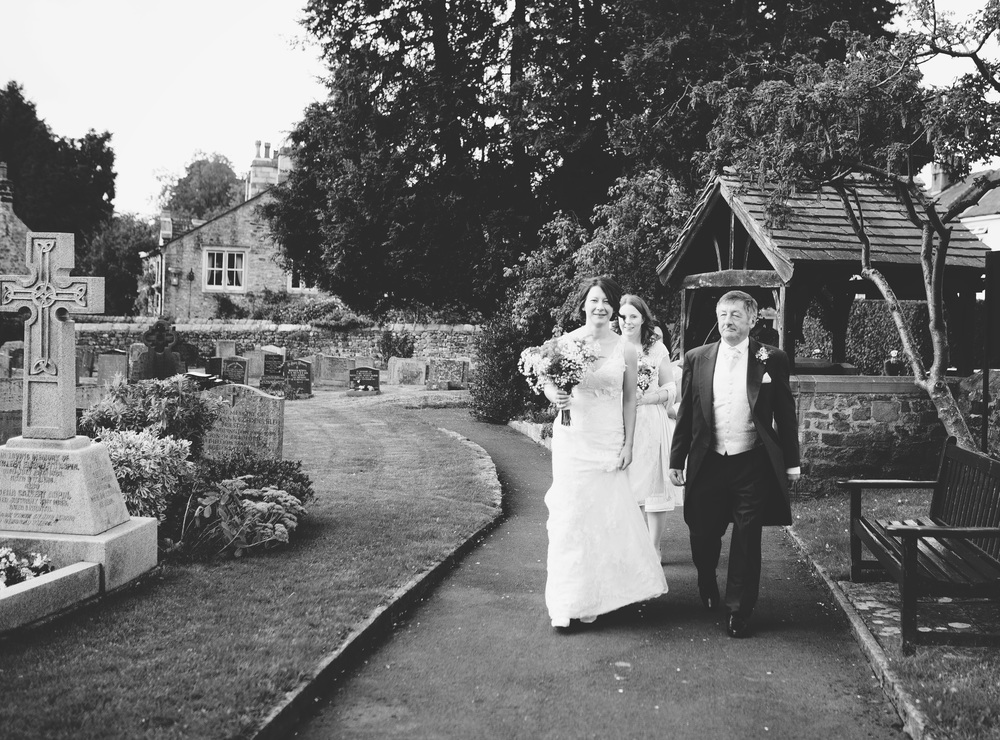 Documentary wedding photograph of the bride walking ot the wedding venue in Ribble Valley.