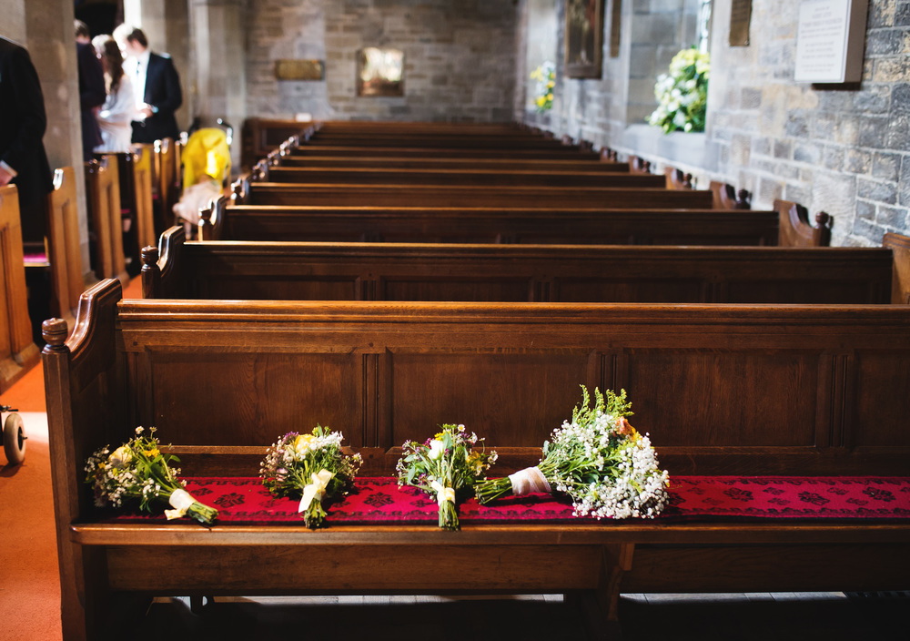 Lancashire wedding photographer- Flowers lay on the church benches.