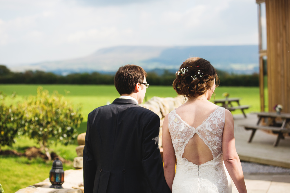 The bride and groom in the grounds of The outbarn at Clough Bottom
