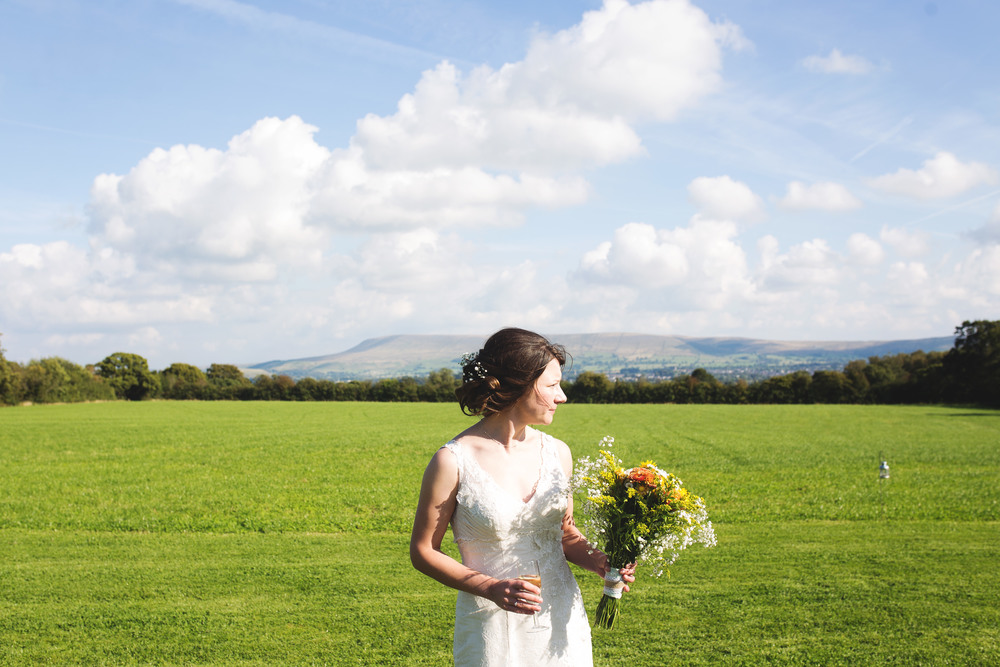 Bride surrounded by blue sky and Pendle Hill.