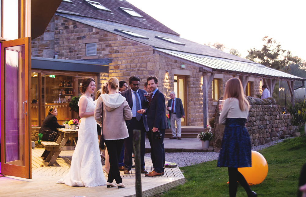 Evening photograph of the bride and groom surrounded by their wedding guests- Country wedding