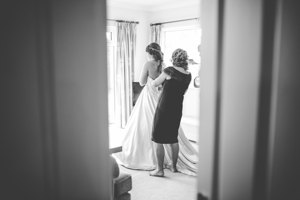 Black and white image of the bride having her dress fasten -Accrington wedding photographer
