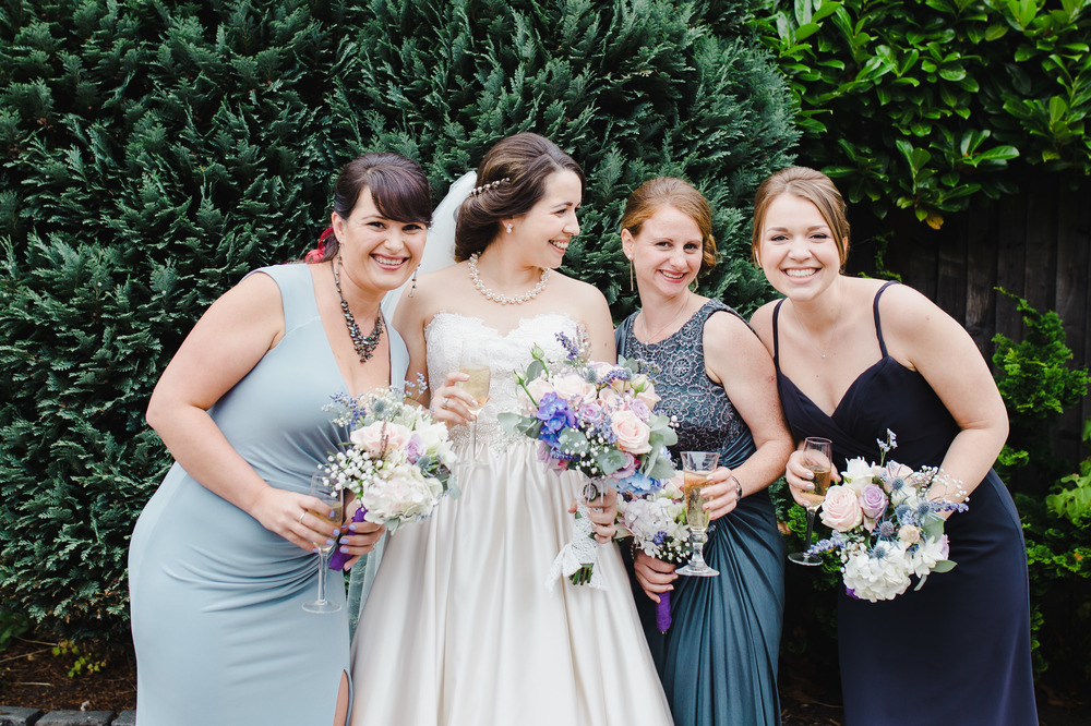 The bride and her bridesmaids laughing outside - Relaxed wedding